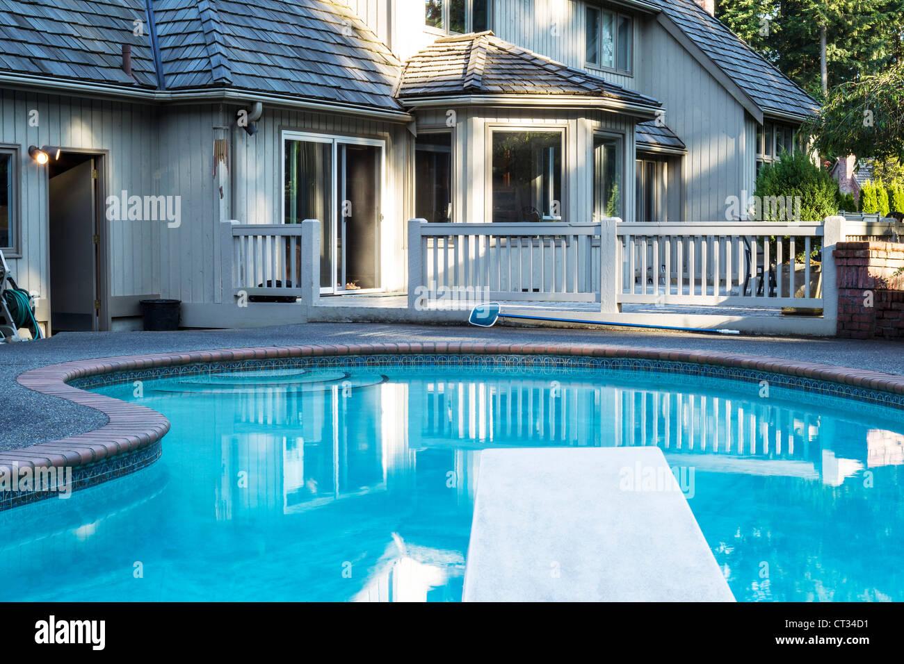 Piscina esterna riscaldata con grande casa in background con alberi verdi Immagini Stock