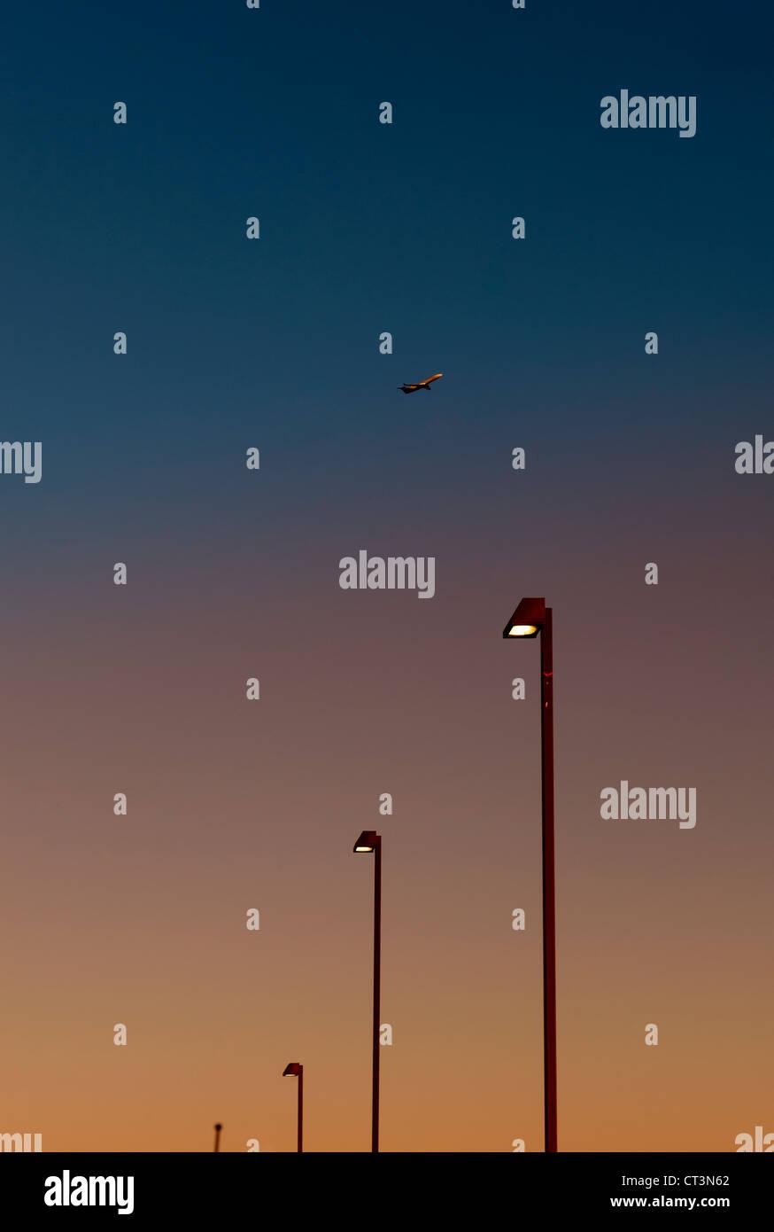 Aeroplano sopra le luci di strada al tramonto Foto Stock