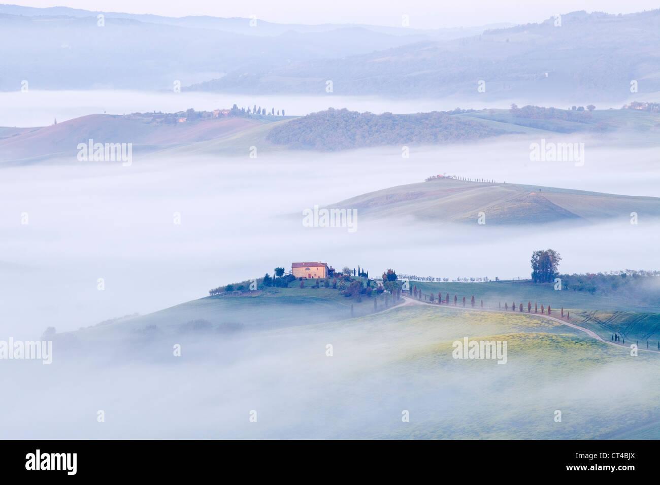 Pienza, Toscana - La mattina presto vista nebbiosa da Pienza verso la Val d'Orcia nel Maggio Immagini Stock