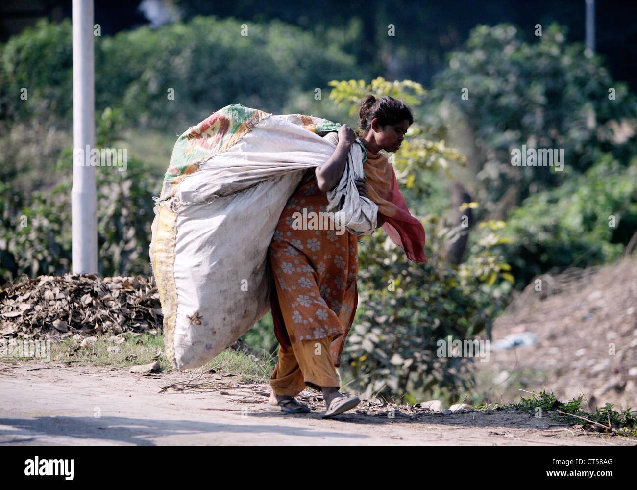 Donna con un sacco di immondizia di plastica nelle strade di Lucknow, Uttar Predesh, India Immagini Stock