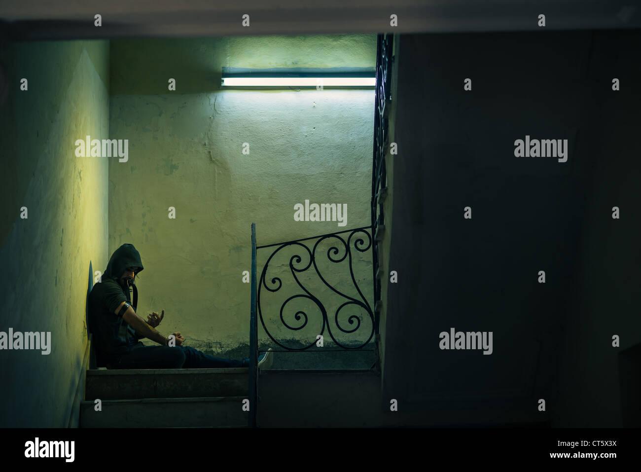 Le questioni sociali e abuso di droga, giovane uomo l'iniezione di eroina e seduti sulle scale. Spazio di copia Immagini Stock