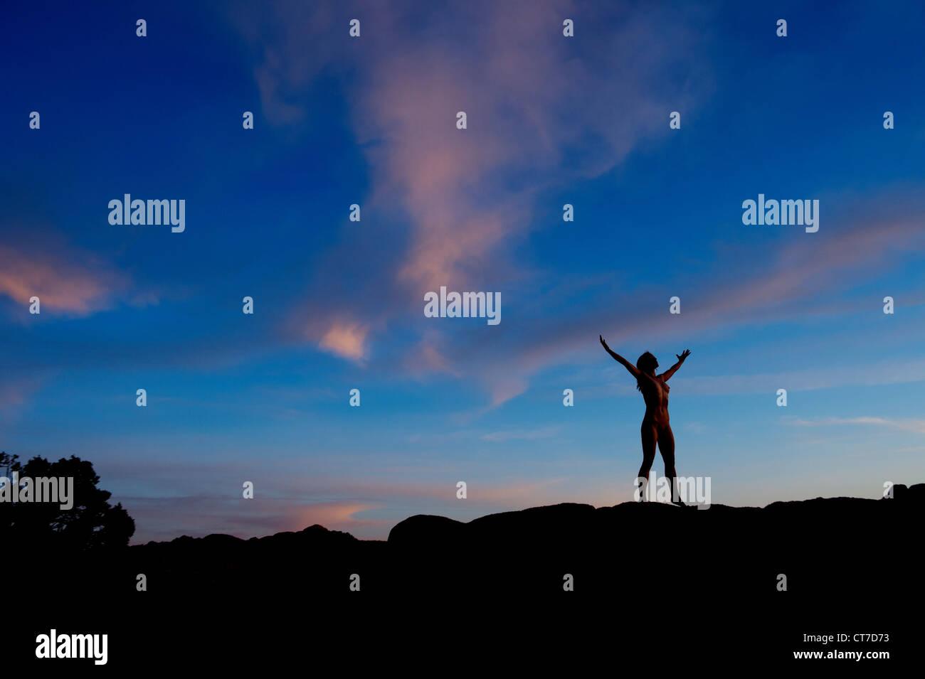 Giovane donna in piedi nel deserto con i bracci aperti, silhouette Immagini Stock