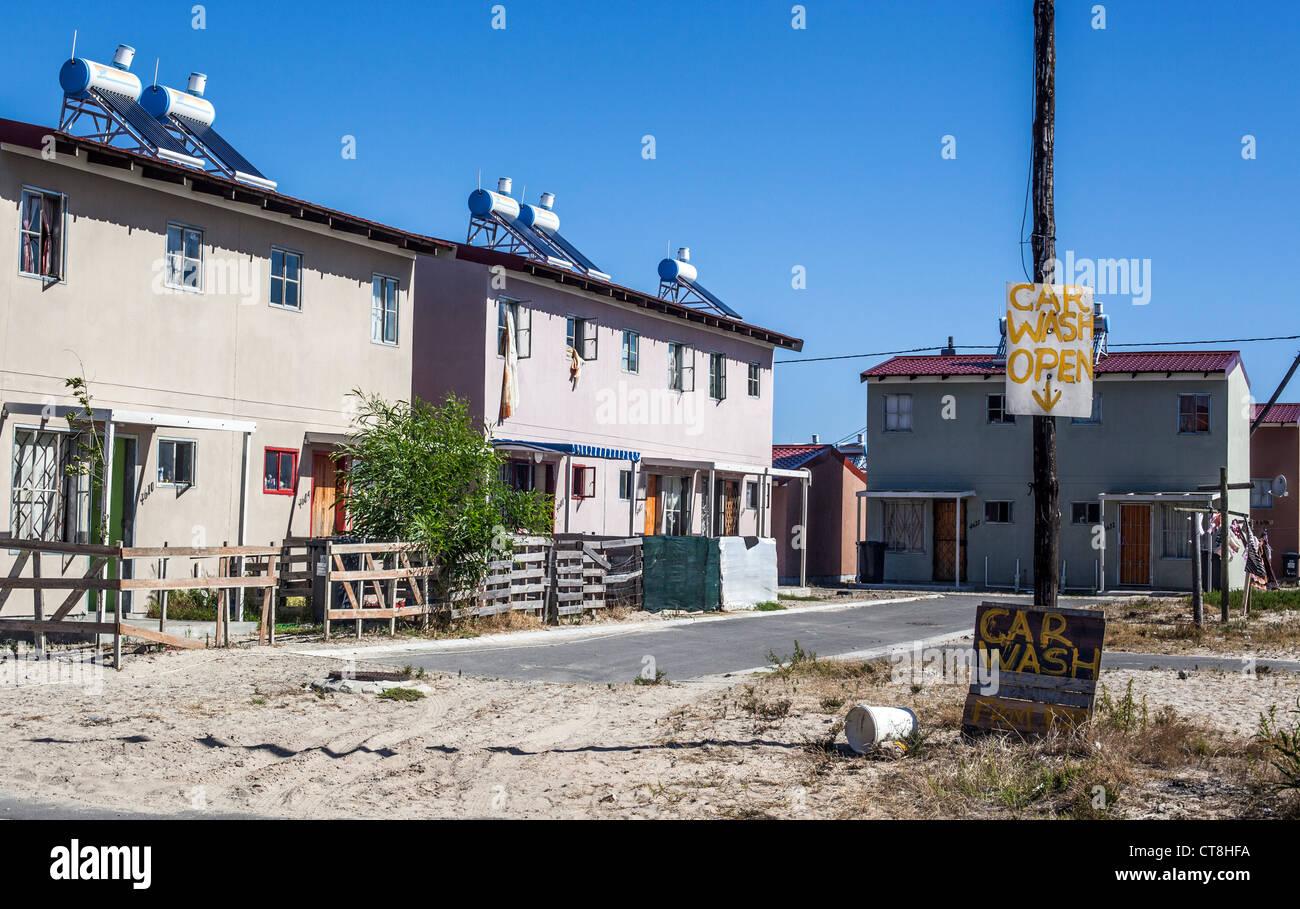 Un informale business (car wash) e case con energia solare per il riscaldamento di acqua in Langa borgata africana, Immagini Stock