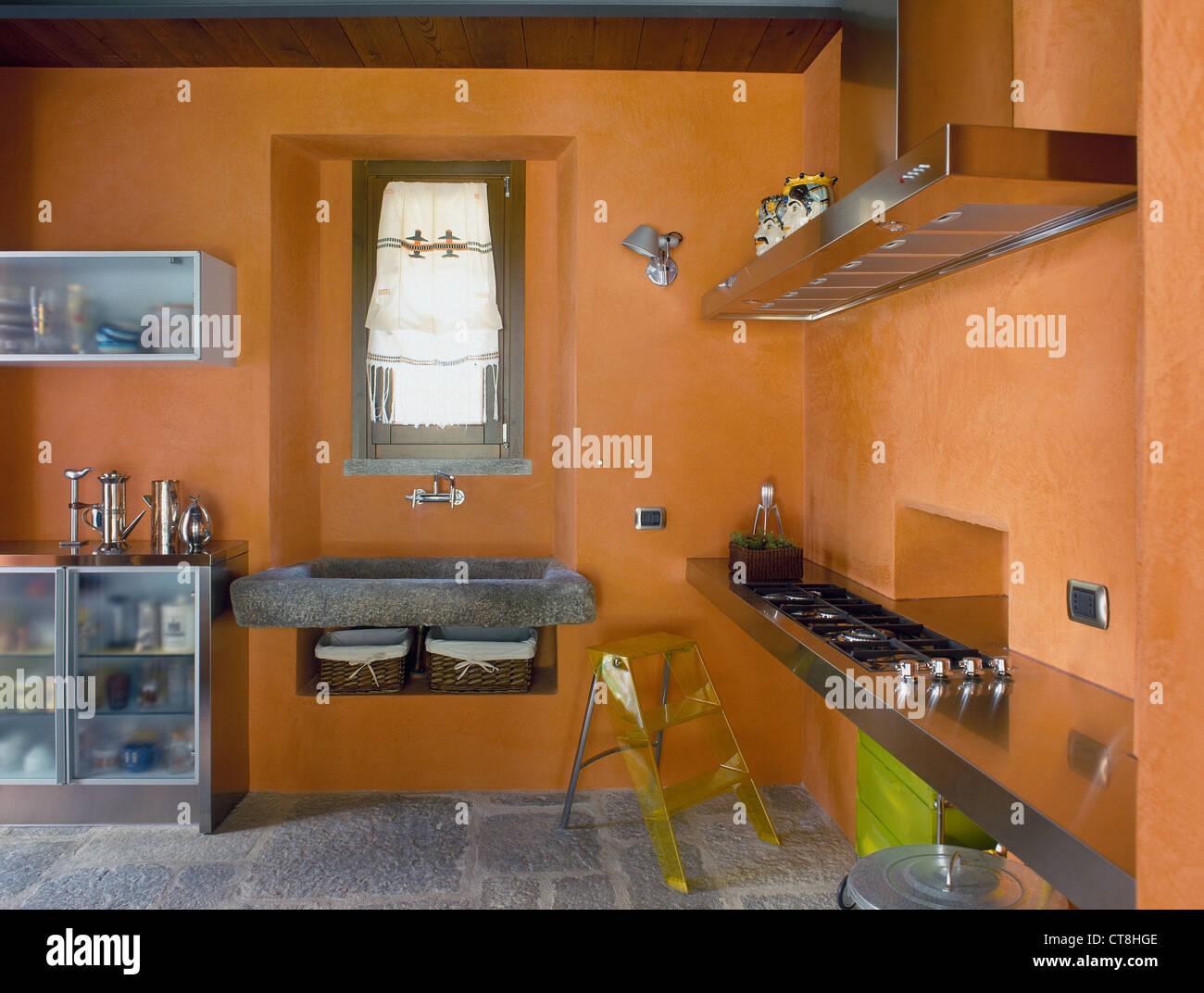Hi-tech cucina con parete arancione, lavandino in pietra e pavimento ...