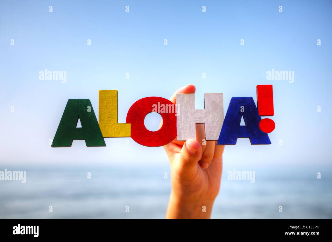"""La femmina mano azienda colorita parola """"Aloha"""" contro sfondo blu Immagini Stock"""