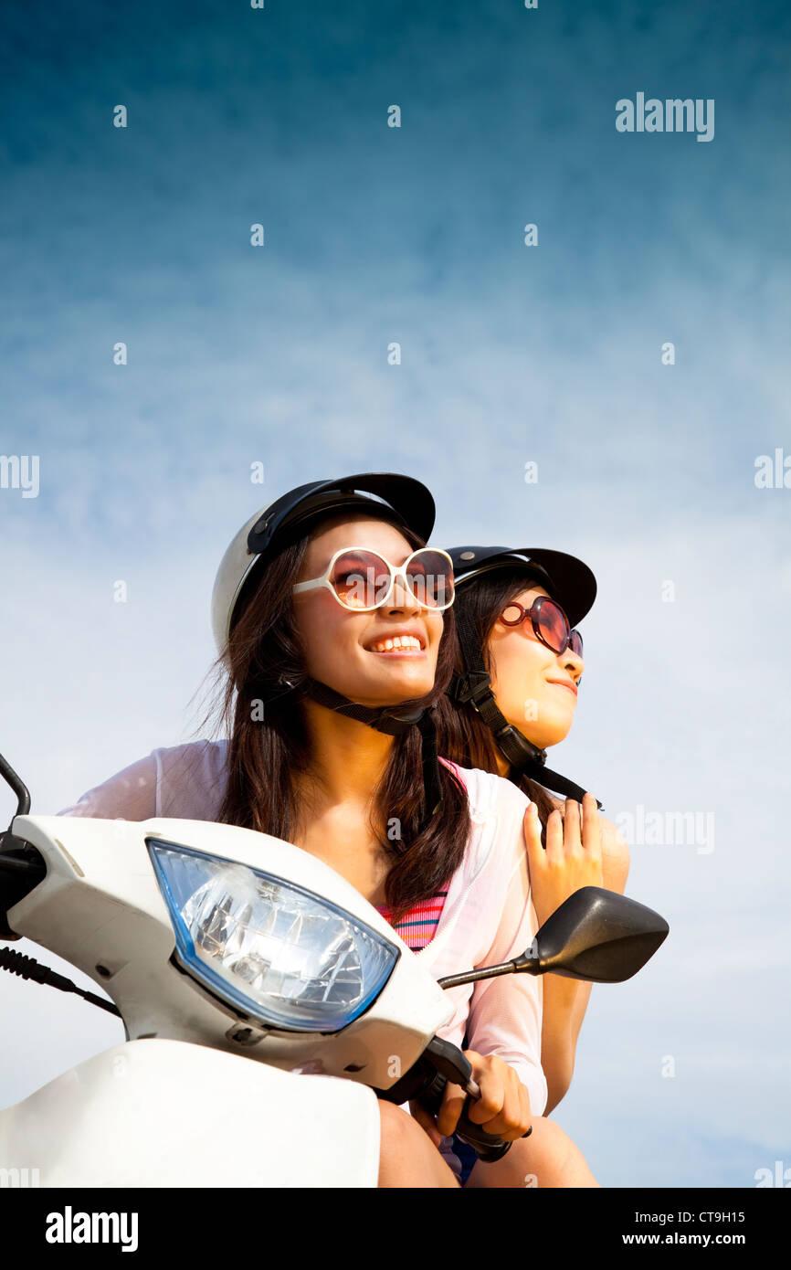 Giovane donna scooter equitazione sulla giornata di sole Immagini Stock
