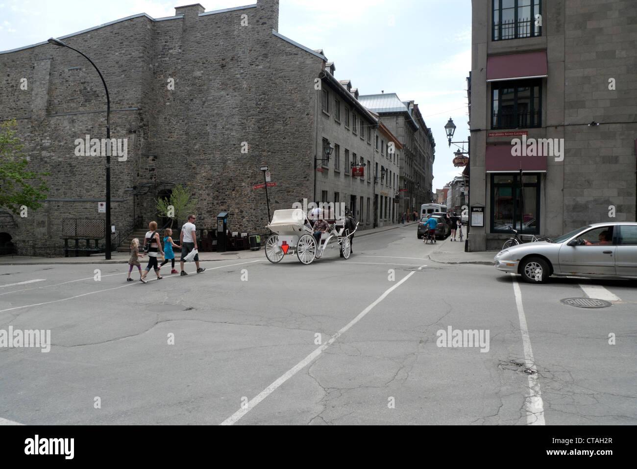 Famiglia attraversando via a Rue Ste. Paolo Est e Boulevard Saint-Laurent con cavallo e carrozza Montreal Québec Immagini Stock
