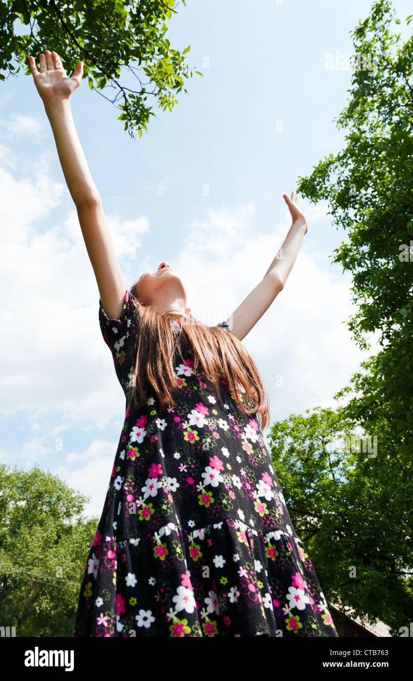 Teen ragazza con le mani alzate contro blu cielo molto nuvoloso Immagini Stock