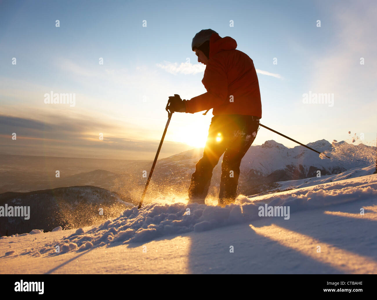 Sciatore con rifiniture a spostarsi verso il basso nella polvere di neve al tramonto; Alpi italiane. Immagini Stock