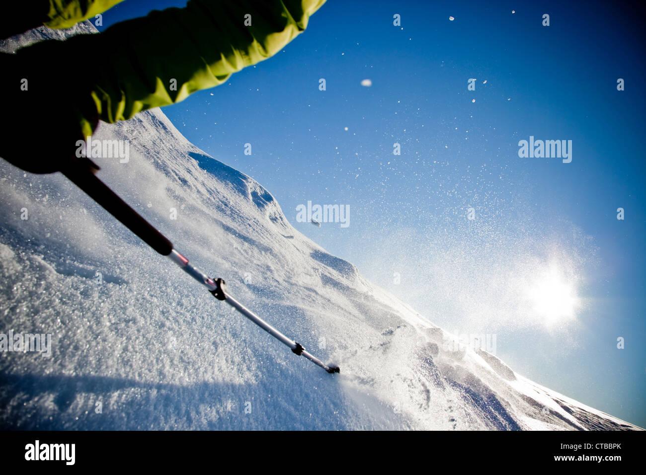 Sciatore con rifiniture a spostarsi verso il basso nella polvere di neve al tramonto (dettaglio) Immagini Stock