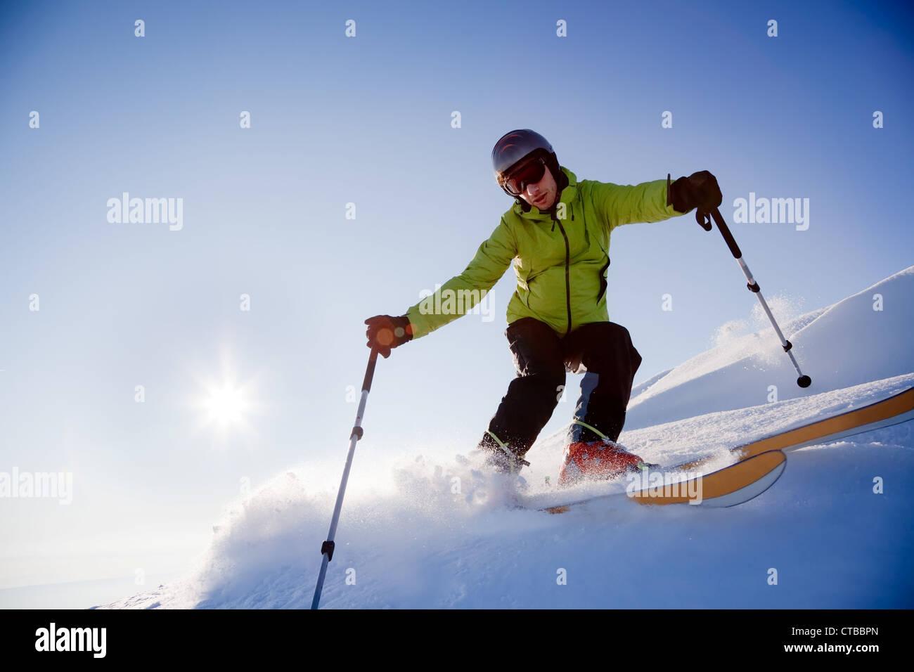Giovane maschio con rifiniture sciatore si sta spostando verso il basso nella polvere di neve al tramonto; Alpi Immagini Stock