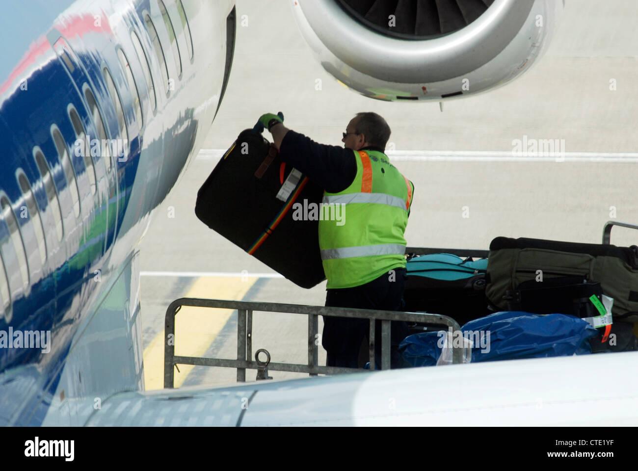 Un gestore di bagagli carichi di sacchetti scarica bagagli valigie per in da un aereo all'aeroporto di Edimburgo Immagini Stock