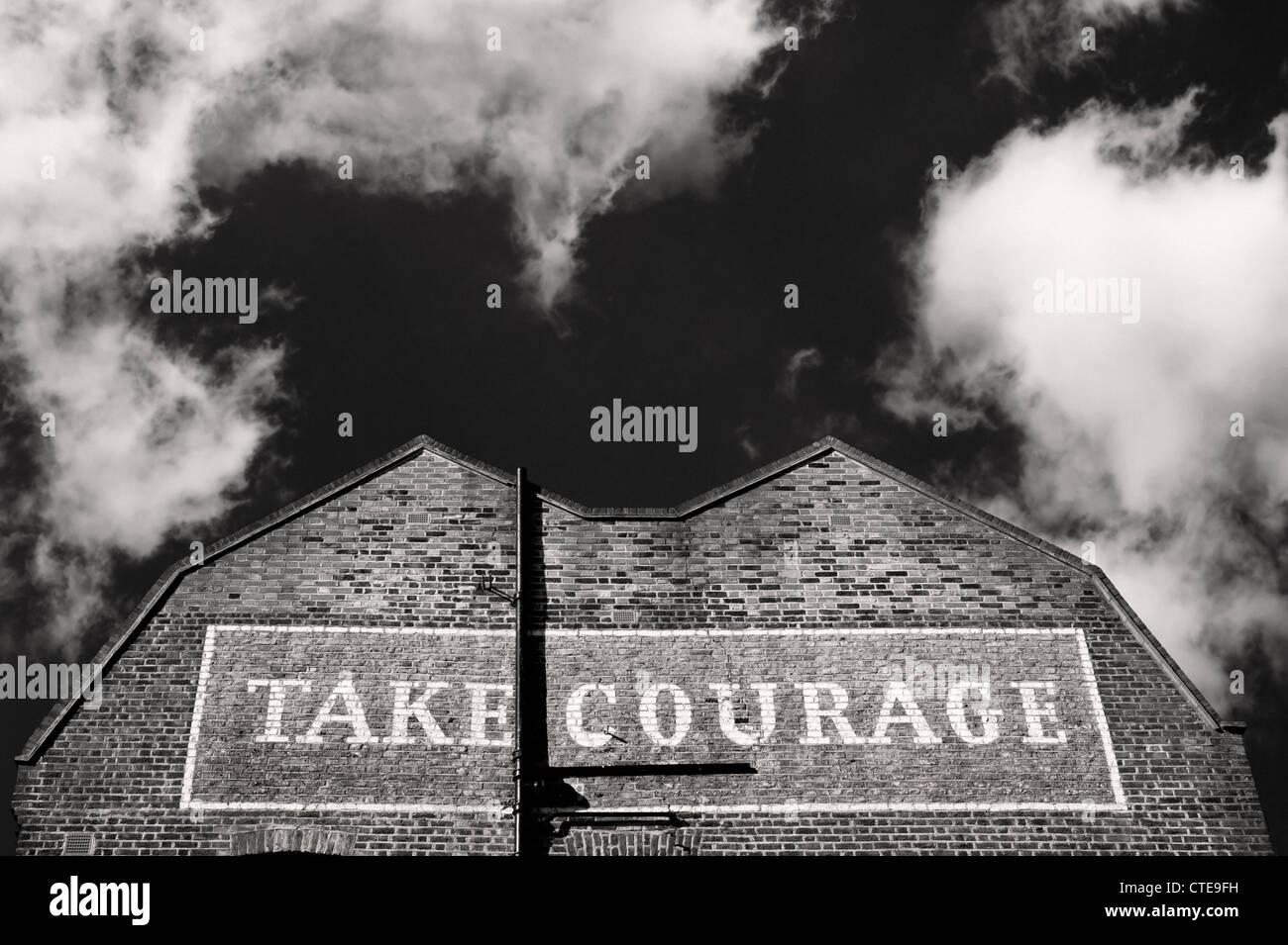 Edificio a Southwark Londra con coraggio dipinto su di esso Immagini Stock