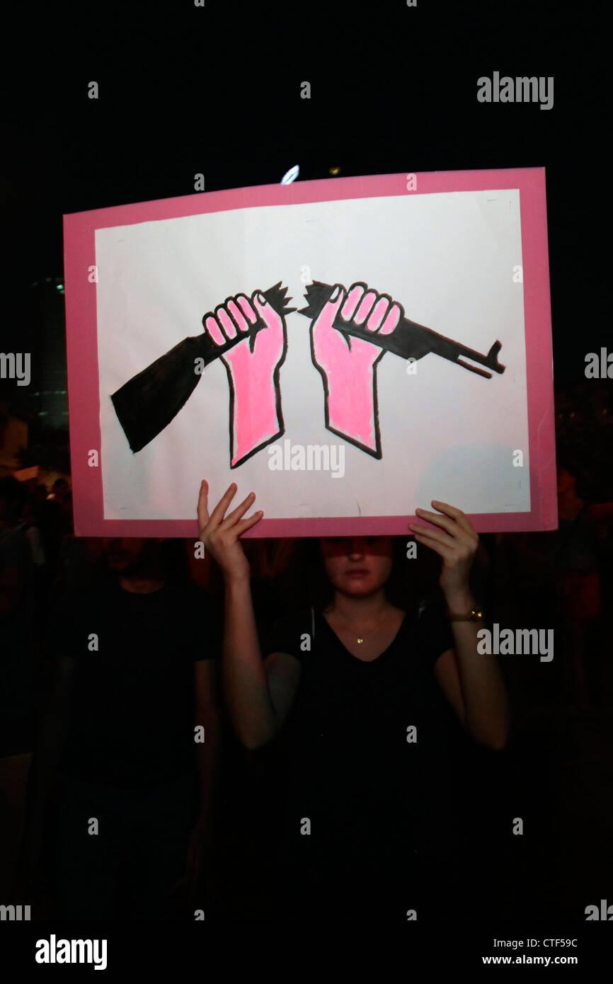 Un dimostrante tenendo un cartello con una figura di un fucile rotto durante il costo della vita protesta a Tel Immagini Stock