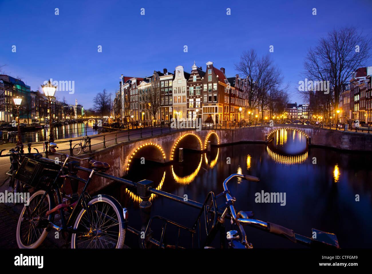 Amsterdam, crepuscolo, attraversamento di canali chiamati Keizersgracht en Leidsegracht. Ponti illuminati, biciclette. UNESCO - Sito Patrimonio dell'umanità. Foto Stock
