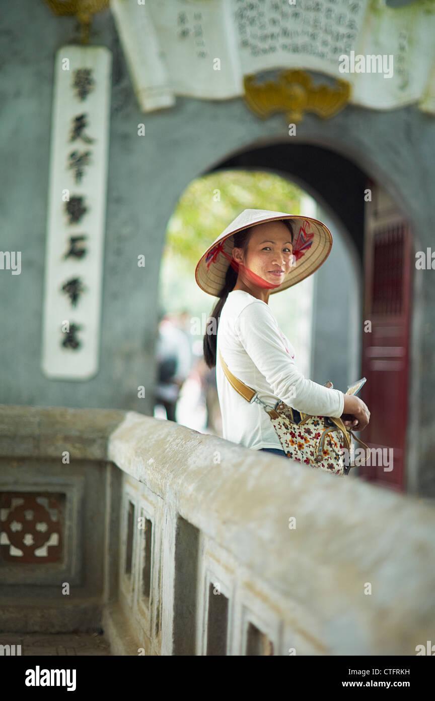 Un ritratto di una donna vietnamita che indossa un nón lá o un tradizionale  vietnamita cappello 970e874da462