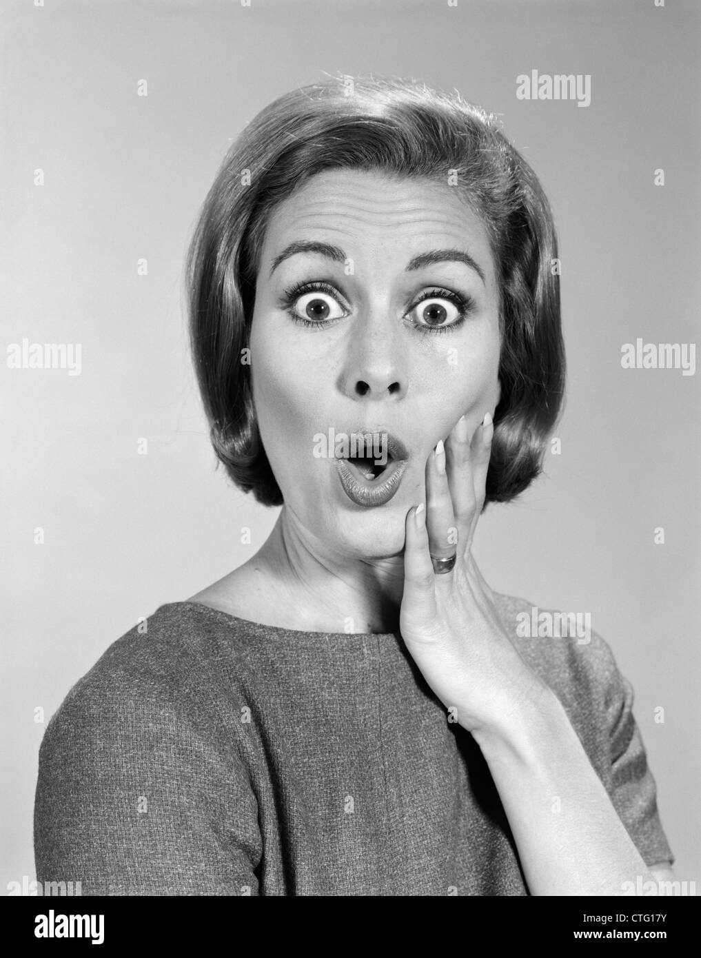 Anni sessanta ritratto donna con la mano sulla guancia guardando la fotocamera con sconvolto l'espressione Immagini Stock