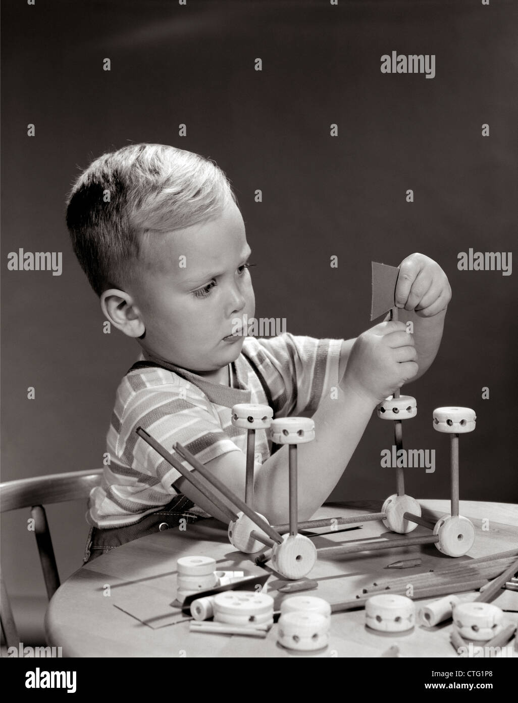 Anni sessanta ragazzo seduto a tavola giocando con TINKER TOY CONSTRUCTION SET Immagini Stock