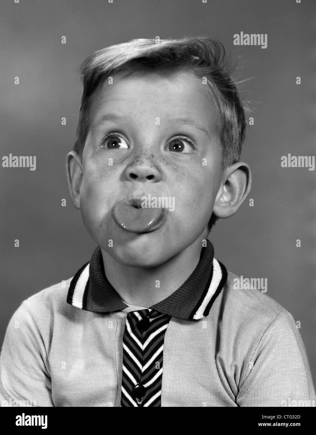 Anni sessanta ritratto ragazzo con capelli biondi & lentiggini con la lingua fuori Immagini Stock