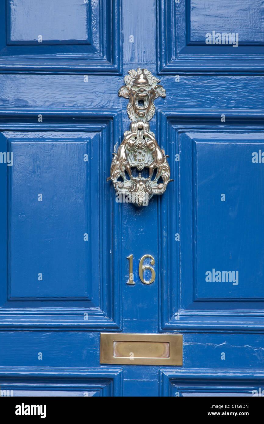 Ottone respingente, numeri e letterbox su una porta blu Immagini Stock