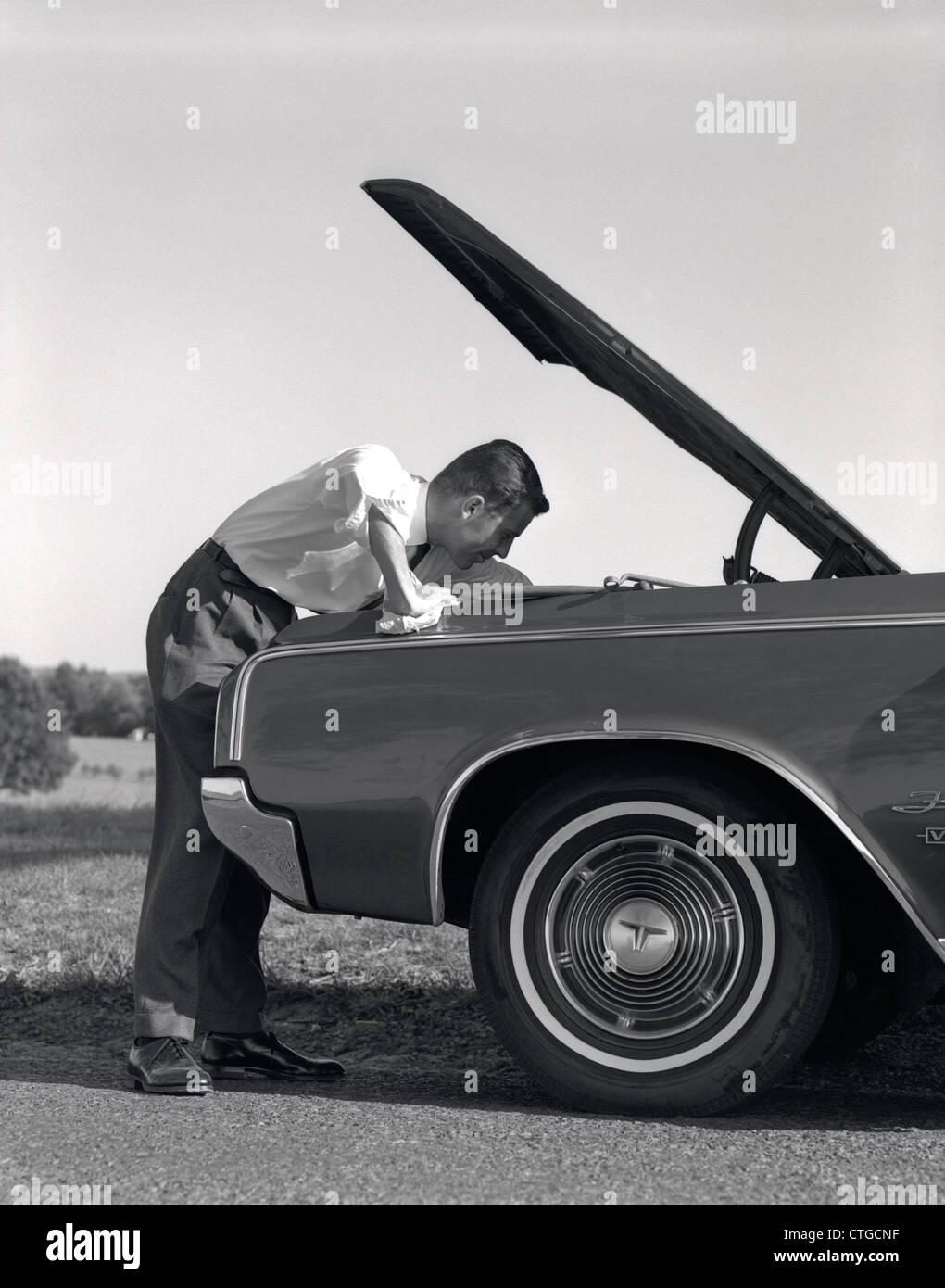 Anni sessanta vista laterale dell'Uomo in camicia e cravatta guardando sotto il cofano della macchina tirata Immagini Stock