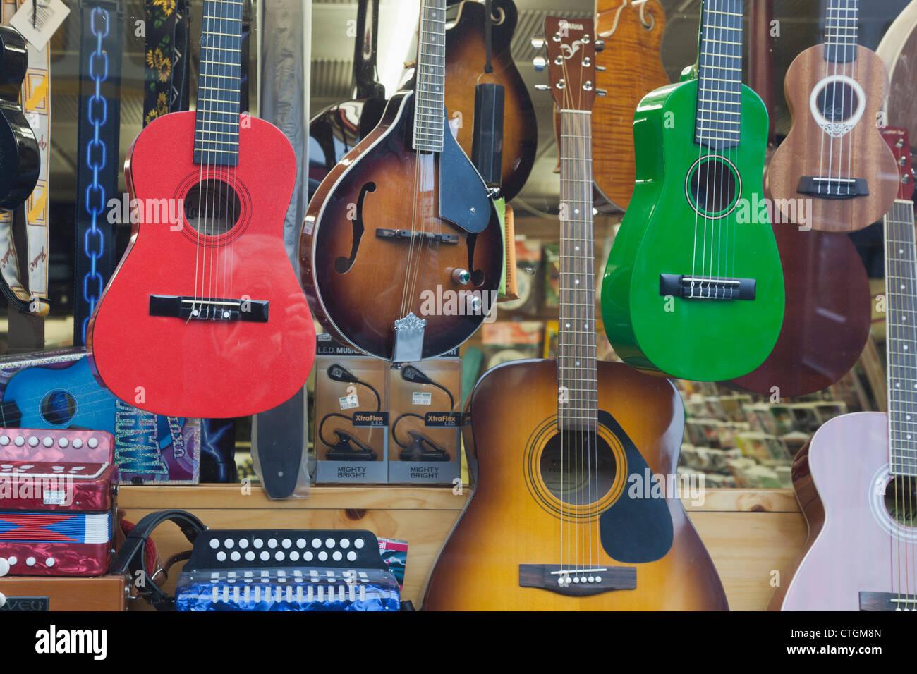 Killarney, nella contea di Kerry, Irlanda. Gli strumenti a corda in vendita in vetrina. Chitarre e Mandolini, ukuleles. Immagini Stock