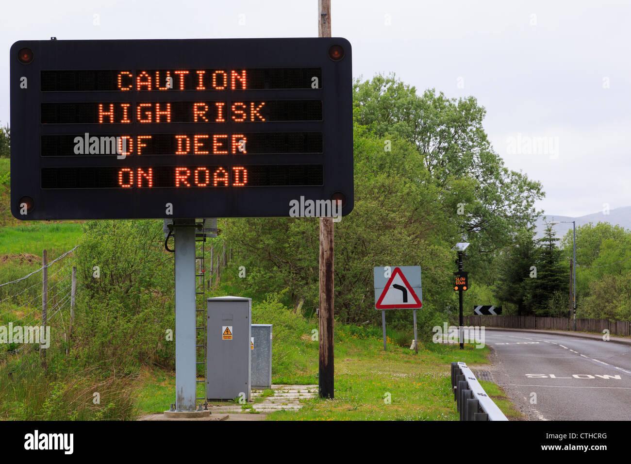 """Segno di matrice su un85 avvertimento """"fare attenzione ad alto rischio di cervo sulla strada' con lenta Immagini Stock"""