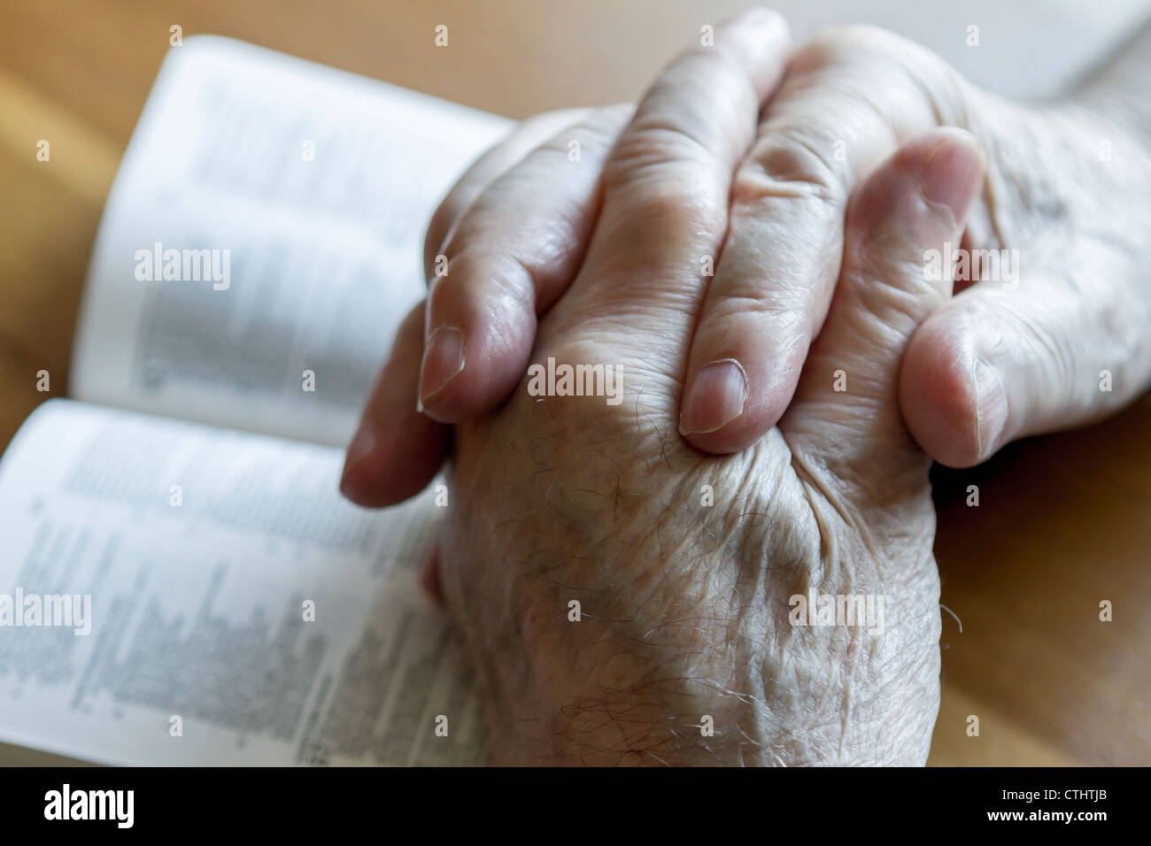 Weathered old man's mani giunte in preghiera sulla Bibbia aperta Immagini Stock