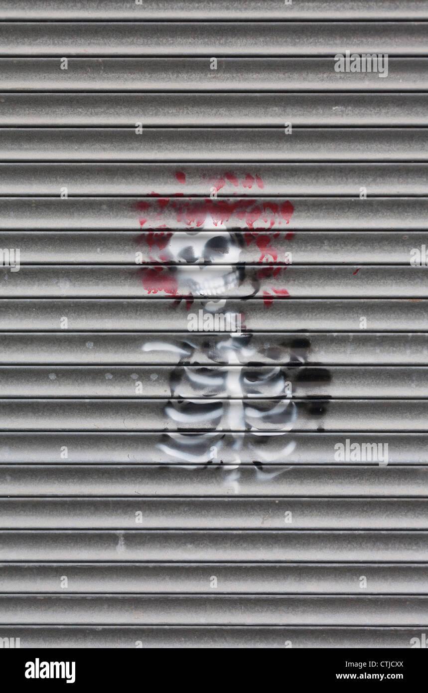 Arte di strada scheletro con capelli rossi graffiti spruzzato sulla serranda metallica Immagini Stock