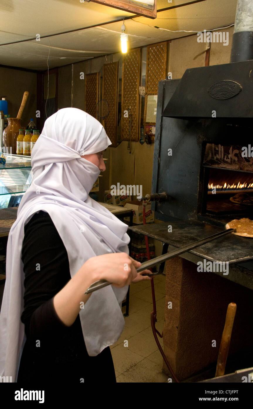 Giovane donna una cottura manaeesh nel panificio Batloun, Shouf montagne del Libano. Immagini Stock