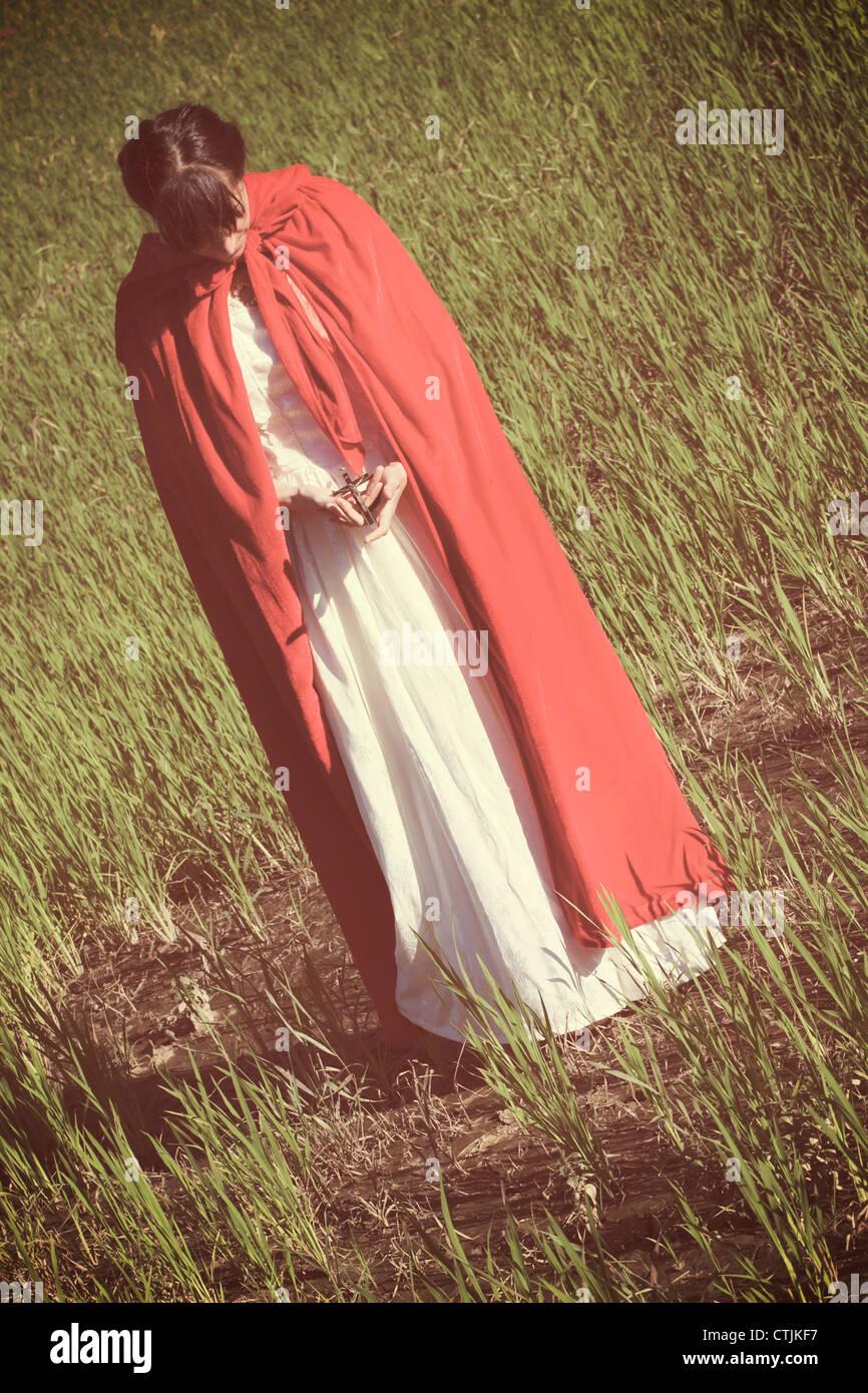 Una donna in un mantello rosso tenendo un crocifisso nelle sue mani Immagini Stock