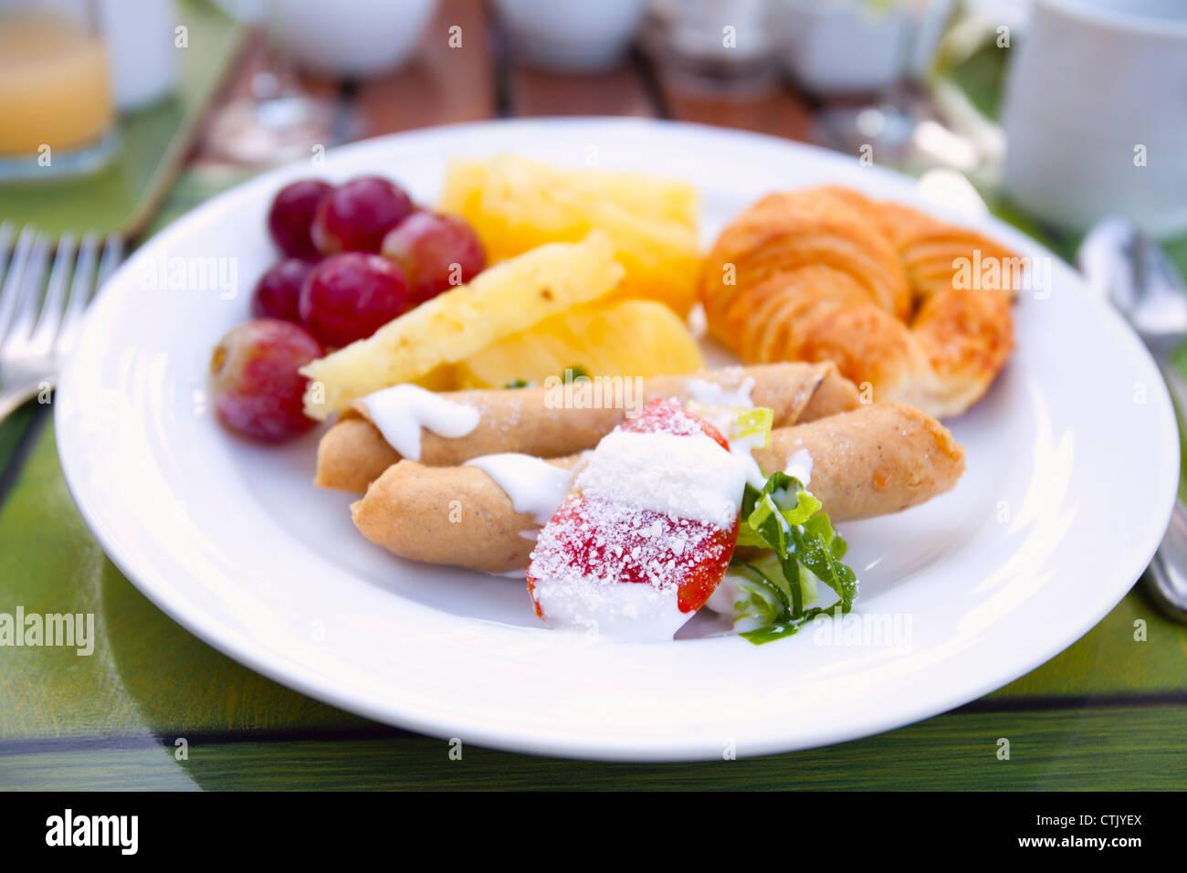 Crêpe di frutta e croissant su una piastra bianca; Puerto Vallarta, Messico Immagini Stock