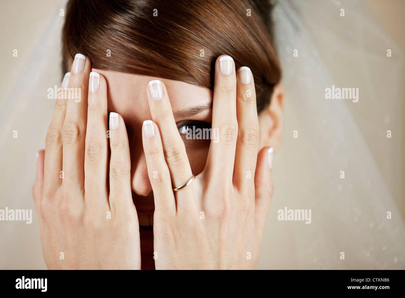 Una giovane sposa che copre il volto con le mani, close up Immagini Stock