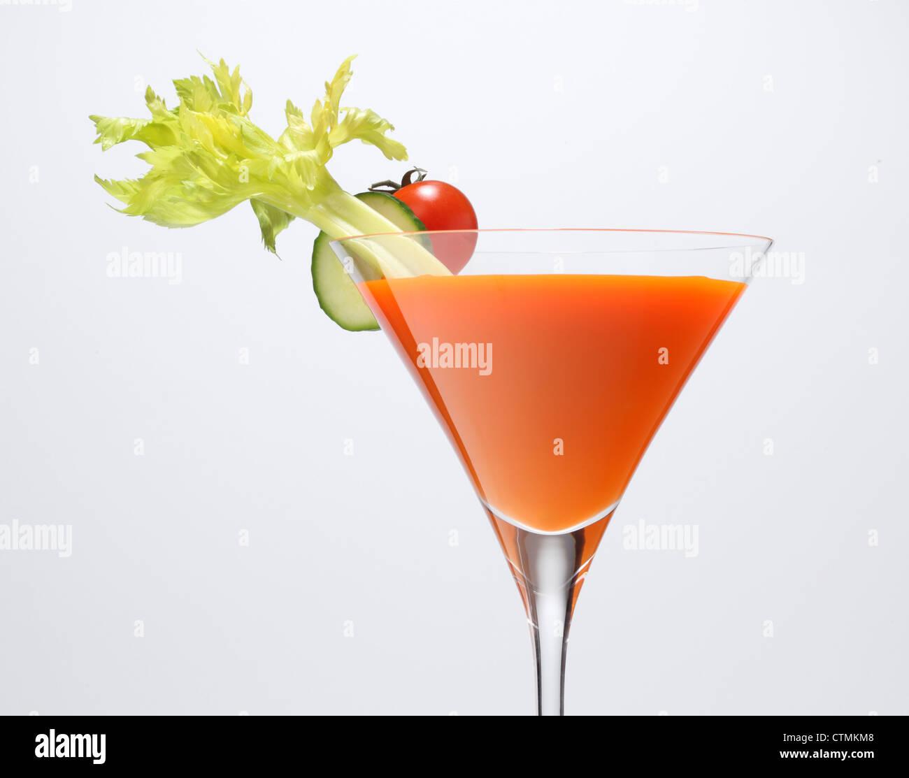 Un arancia succhi di verdura in un calice con verdura guarnire. La costa di sedano, Cucumber Slice e pomodoro ciliegino. Foto Stock