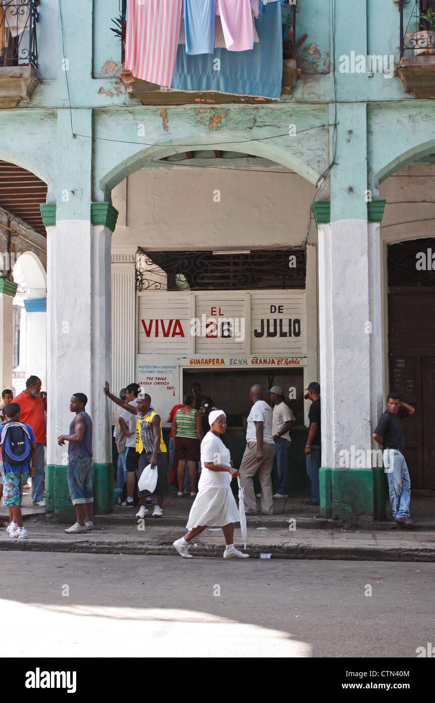 Una signora con un ombrellone tutti vestiti di bianco passeggiate passato un negozio nel centro di Avana, Cuba Foto Stock