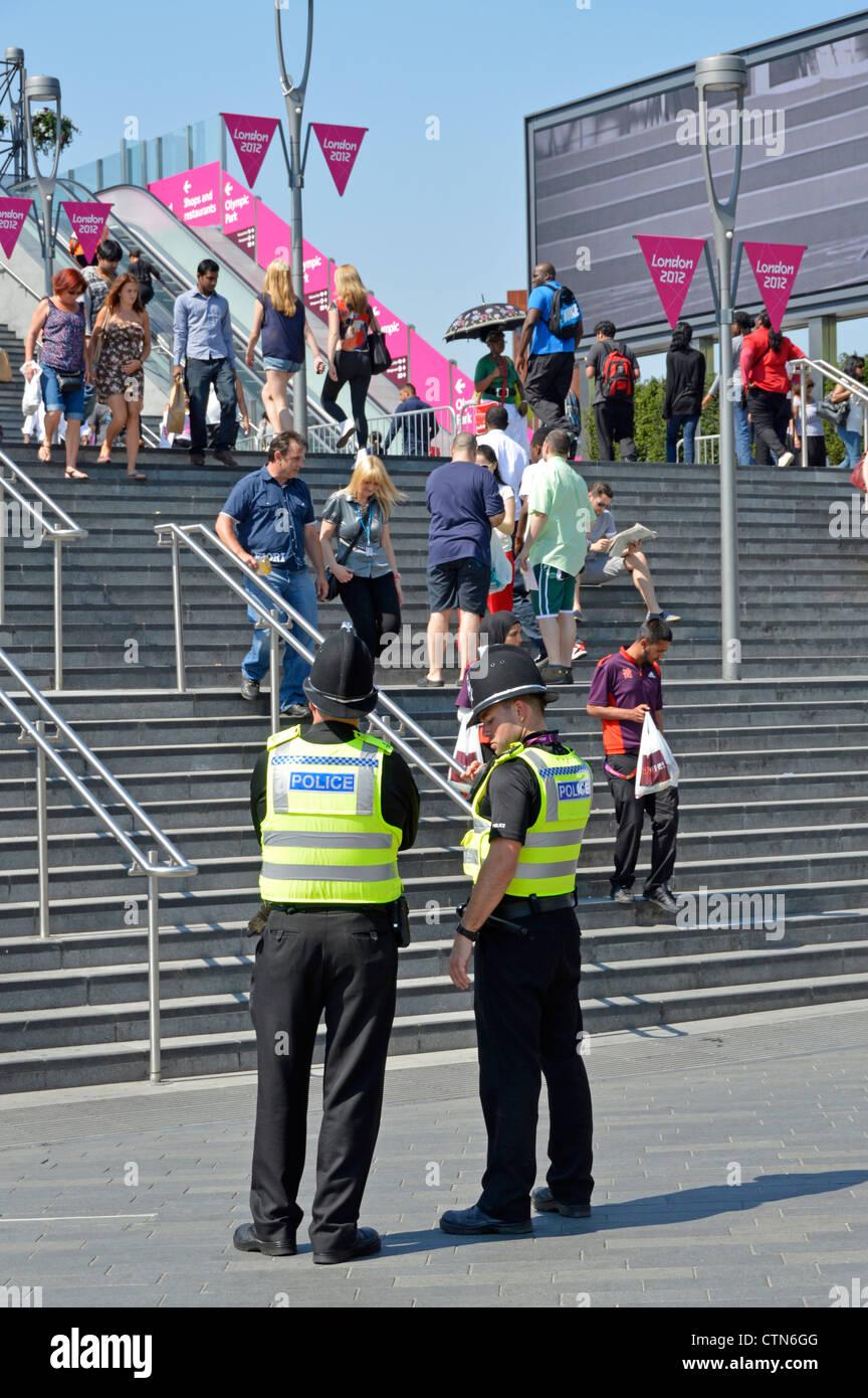 Gli ufficiali di polizia in servizio all'entrata passi per il 2012 Olympic Park e il Westfield Stratford City Immagini Stock