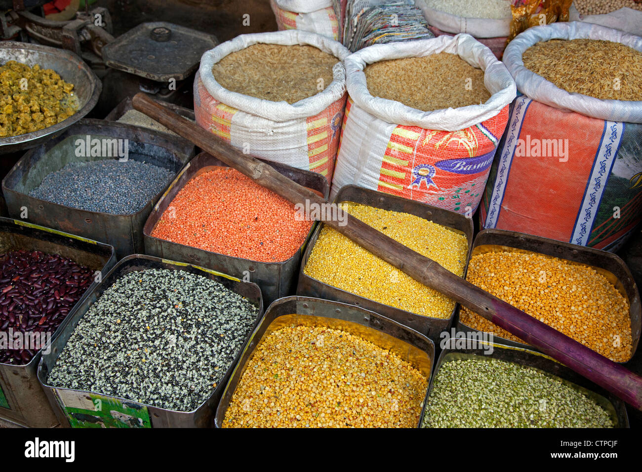 Colorato ingredienti alimentari come mais, fagioli, riso e spezie in sacchetti e lattine al mercato di Agra, Uttar Immagini Stock