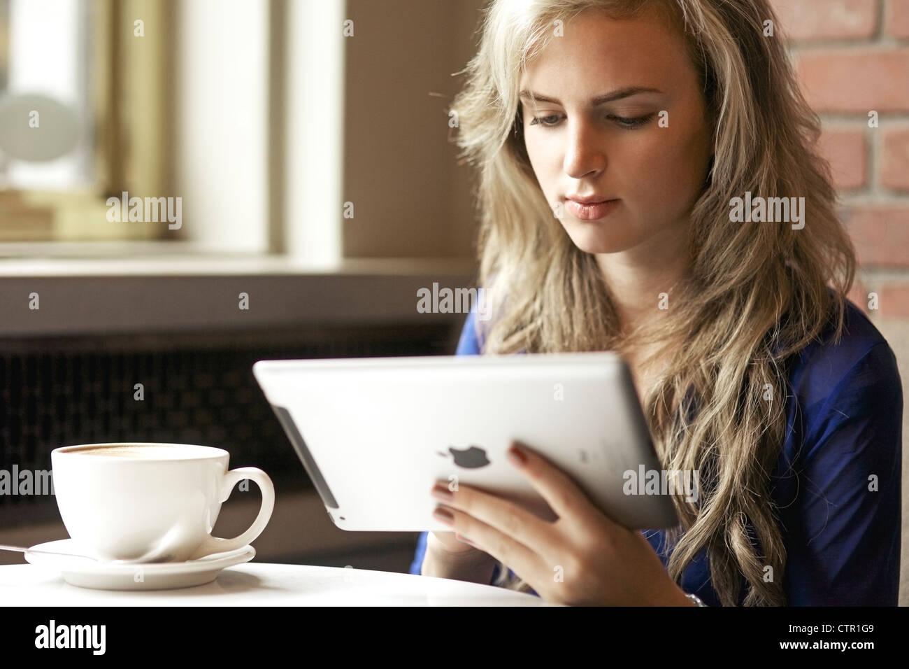 Bella giovane donna lettura dal suo ipad mentre godendo il suo cappuccino con un coffee shop Immagini Stock