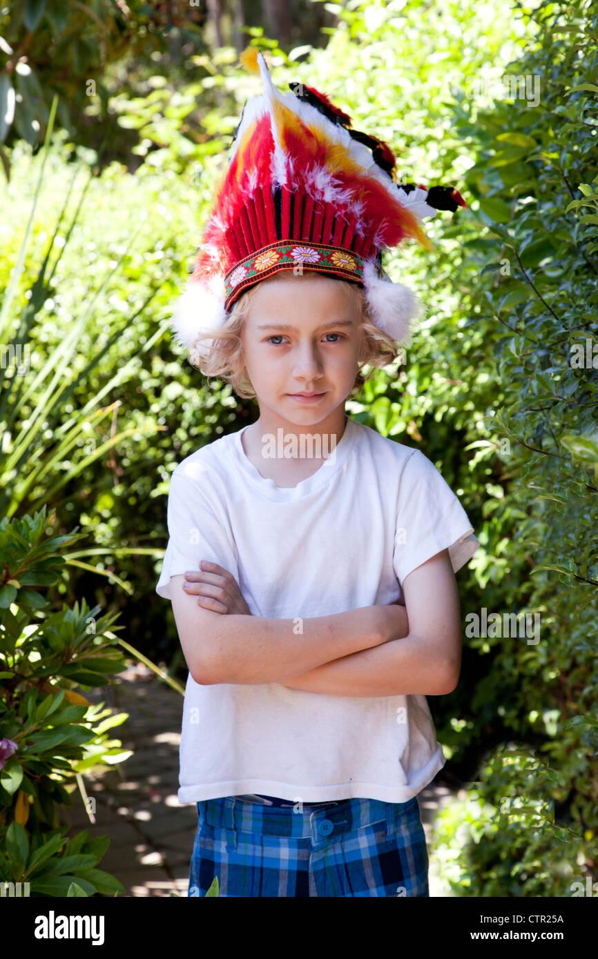 Un ragazzo biondo indossando un giocattolo copricapo indiano. Immagini Stock