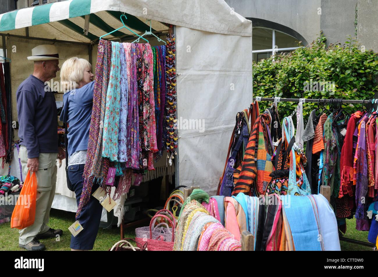 Una donna acquisto di un commercio equo vestiti da uno stallo a una fiera di paese Ceredigion nel Galles Cymru REGNO Immagini Stock