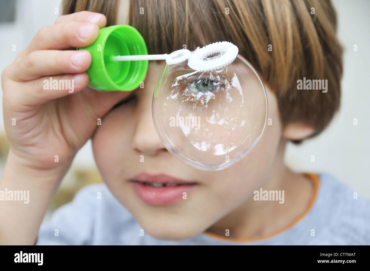 Un ragazzo giocando con bolla di soffiante Immagini Stock