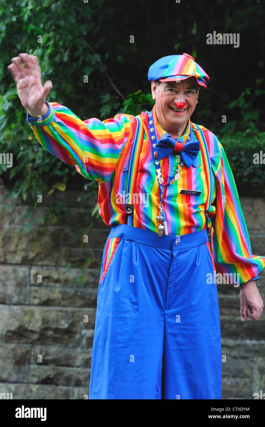 Un uomo vestito come un clown in abiti colorati e naso rosso a Pollok Park  il giorno della famiglia a Glasgow 2a80d007b33
