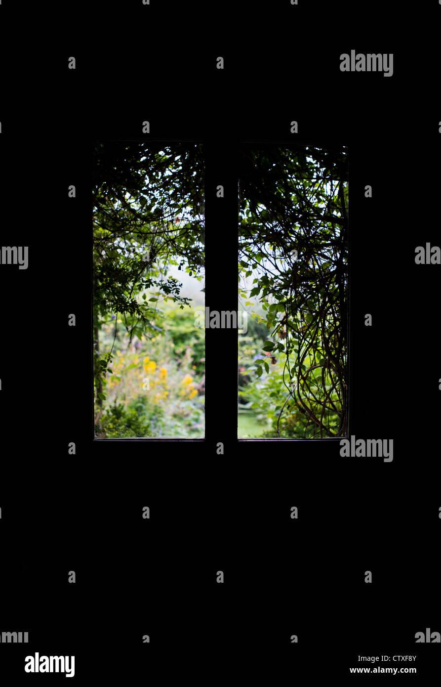 Ricoperta con vista giardino attraverso le finestre di vetro in una porta anteriore. Silhouette Immagini Stock