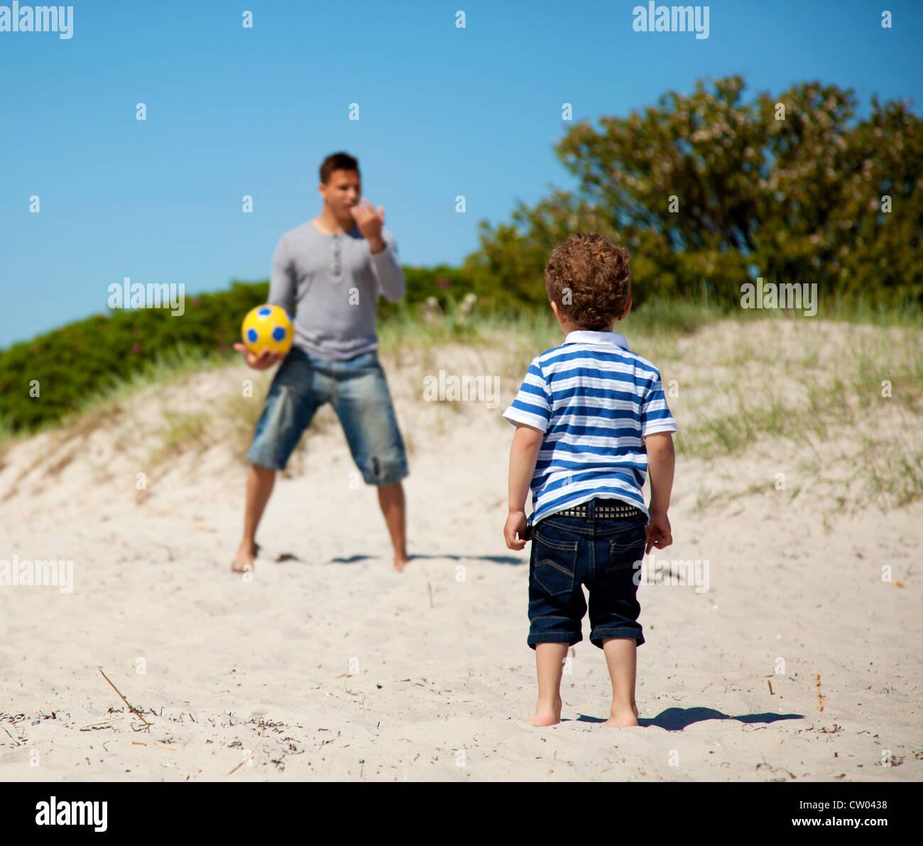 Bambino guardando al suo papà insegnare a lui come a giocare a calcio all'aperto Immagini Stock