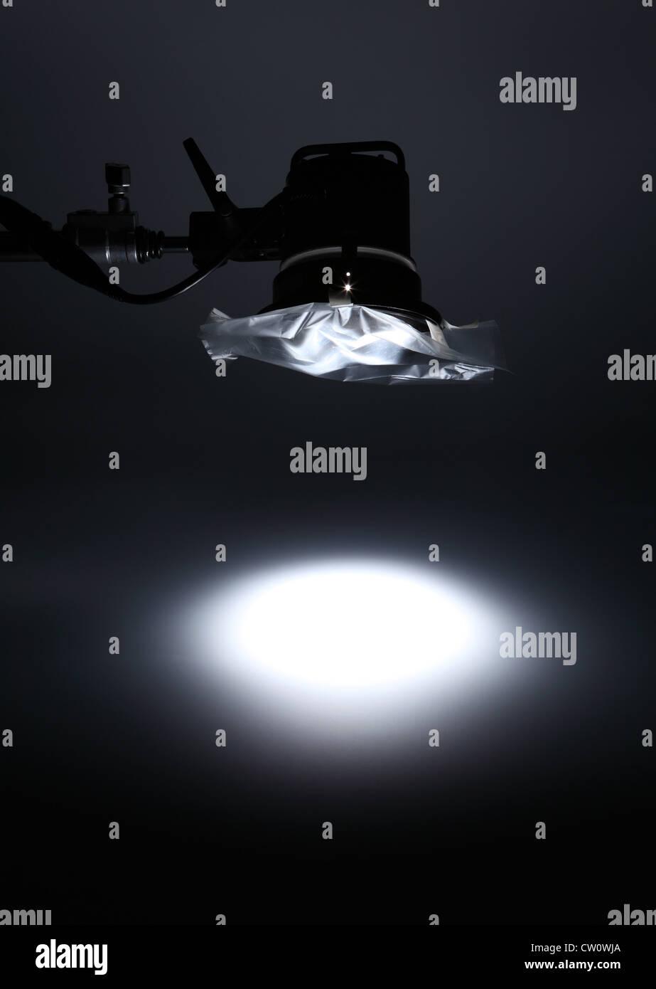 Una luce fotografici da sopra la creazione di un faretto bianco su un vuoto di sfondo scuro. Immagini Stock