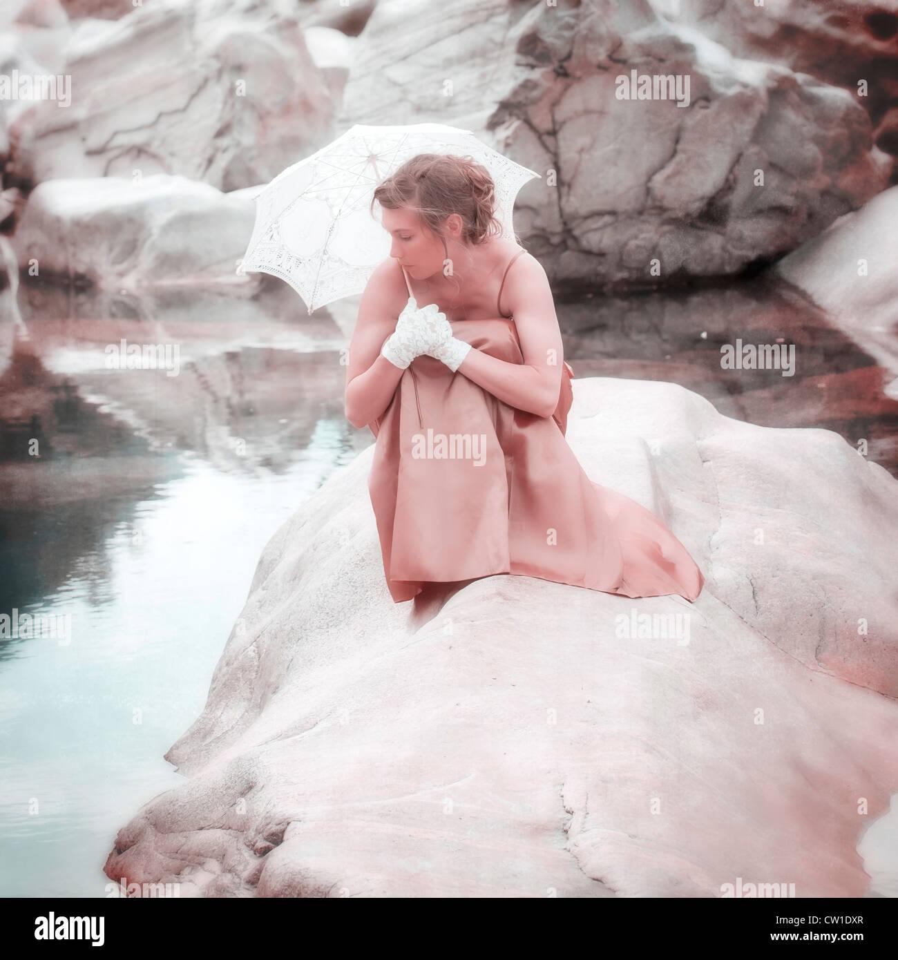 Una giovane donna seduta su una roccia in acqua con un ombrellone Immagini Stock