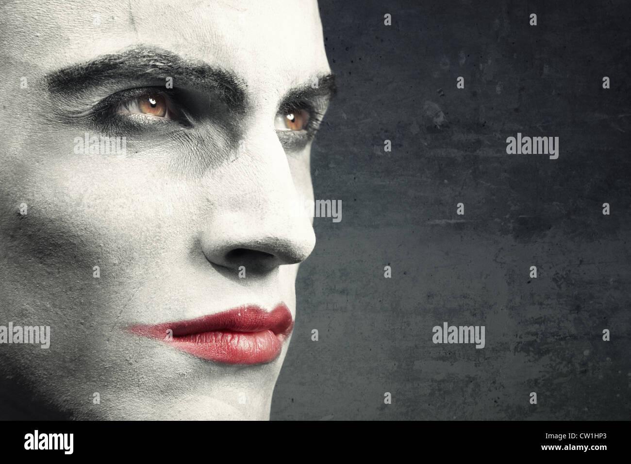 Uomo con vampiro trucco al buio su un grungy sfondo. Trucco naturale e lo sfondo. Il testo può essere aggiunto Immagini Stock