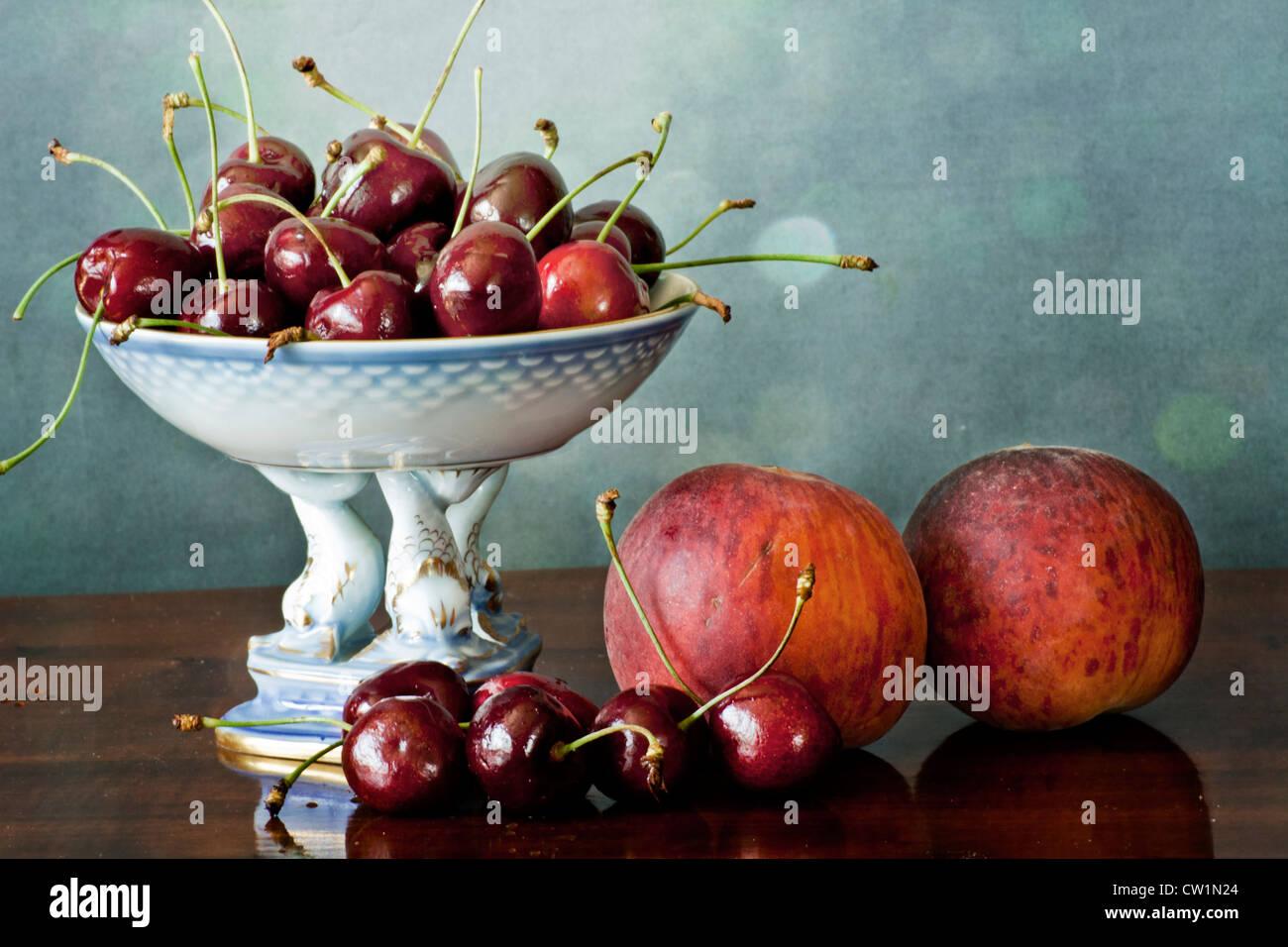 Interno con il rosso scuro ciliegie su un vassoio di Cina e le pesche su una tavola di legno lucidato tabella Immagini Stock
