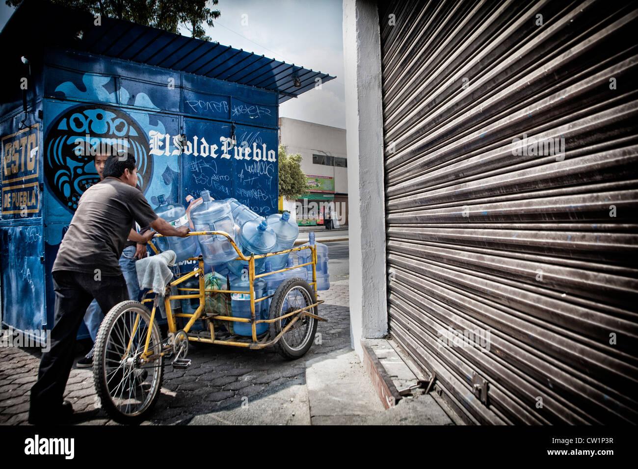 L'uomo spingendo il carrello vuoto di bottiglie di acqua in Puebla, Messico Immagini Stock