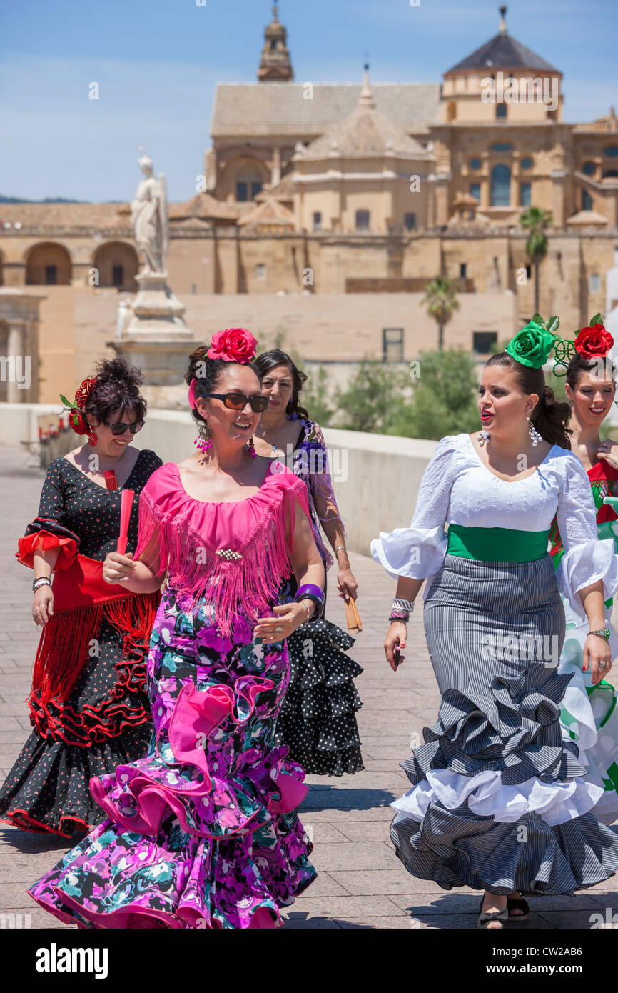 Cordoba Ponte Romano. Le donne che vanno a maggio Feria festival, vestito in Spagnolo tradizionale traje de gitana, Immagini Stock